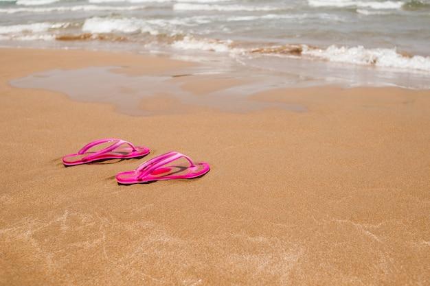 Chanclas rosas sobre una arena clara. textura de arena clara.