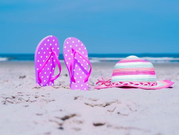 Chanclas y sombrero de colores sobre arena tropical