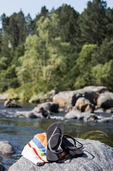 Chanclas y toalla en piedra cerca del agua