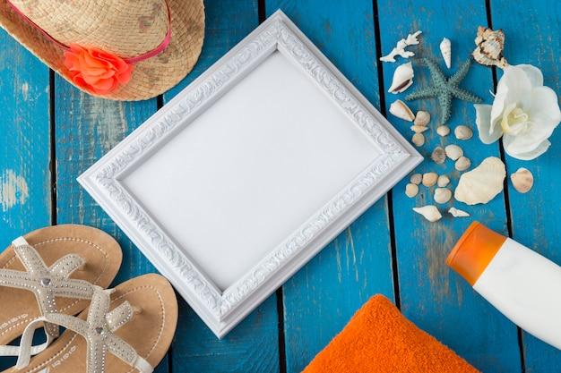 Chanclas, toalla, sombrero, crema solar, conchas, estrellas de mar, orquídeas y marco de fotos