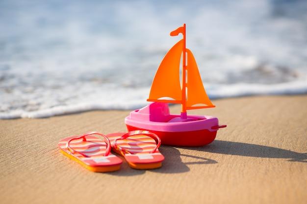Chanclas y velero de juguete en la playa concepto de viaje y vacaciones de verano