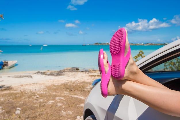Chanclas desde la ventana de un automóvil en la playa tropical de fondo