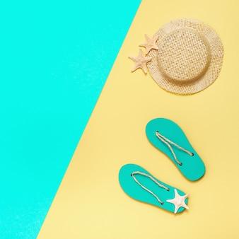 Chanclas de verano, sombrero de paja y pequeñas estrellas de mar sobre una superficie de papel brillante