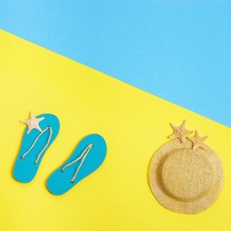 Chanclas de verano, sombrero de paja y pequeñas estrellas de mar