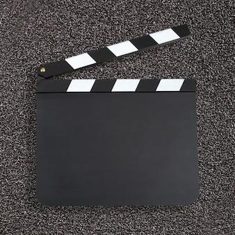 Chapaleta de producción de películas en blanco sobre fondo oscuro con c
