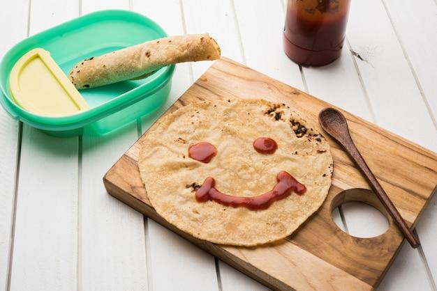 Chapati roll con salsa de tomate o gelatina de mermelada de frutas con cara sonriente, menú de comida favorita de los niños indios para la escuela tiffin box, enfoque selectivo