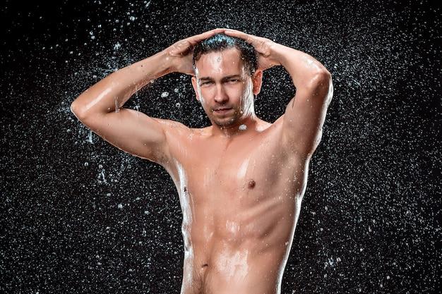 El chapoteo del agua en la cara masculina