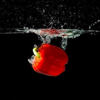 Chapoteo de pimiento rojo en agua clara