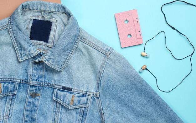 Chaqueta de jeans, cassette de audio, auriculares de vacío en superficie azul pastel. medios retro, amante de la música, años 80. vista superior, endecha plana