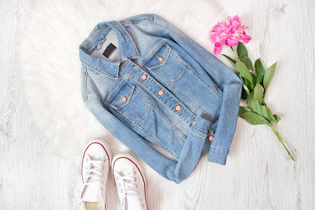Chaqueta de jeans, zapatillas blancas y peonía rosa.