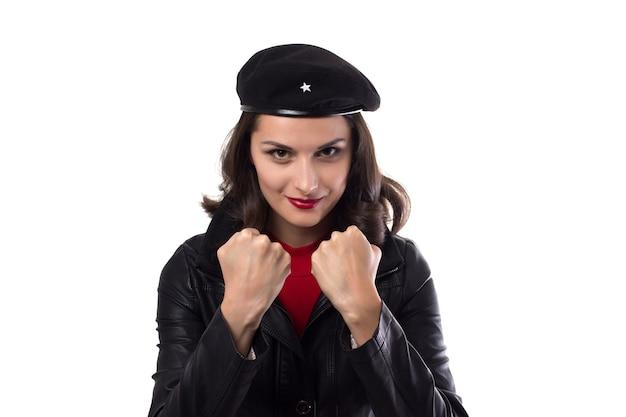 Chaqueta negra de mujer joven, suéter rojo y sombrero con una referencia a un revolucionario mirando a puerta cerrada, demuestra sus puños y sonríe sobre un fondo blanco con espacio de copia