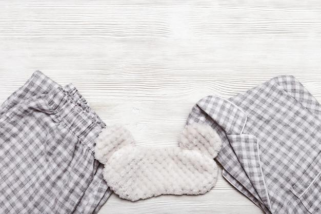 Chaqueta y pantalón doblados y máscara para dormir en la mesa de madera,