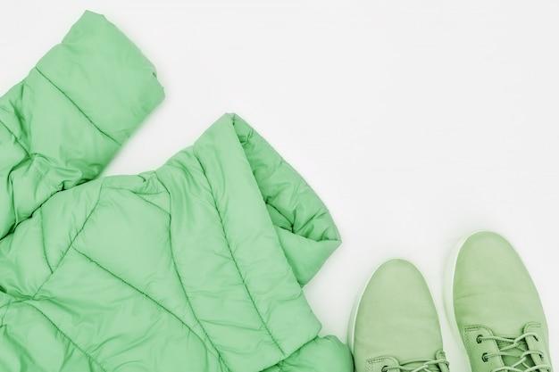 Chaqueta verde y botas sobre un fondo blanco.