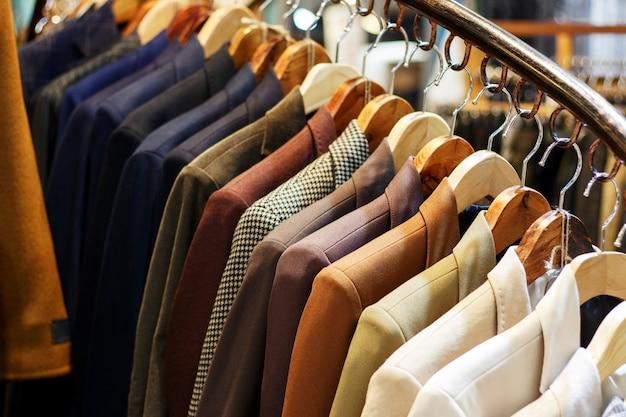 Chaquetas de hombres con estilo en perchas en la tienda, primer plano