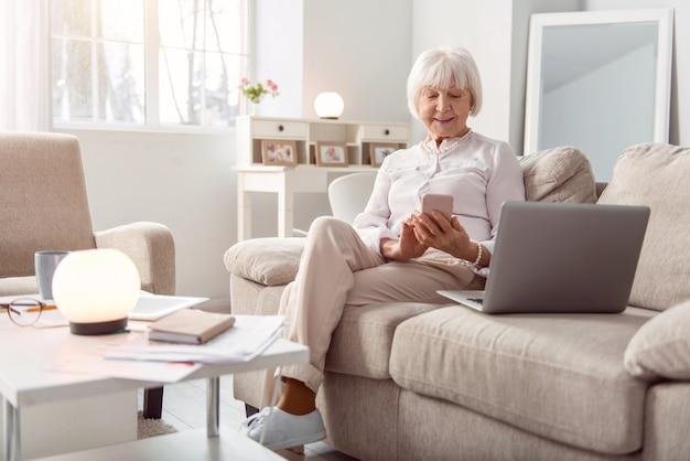 Charla agradable. hermosa anciana enviando mensajes de texto en su teléfono y sonriendo felizmente mientras está sentada en el sofá de la sala de estar