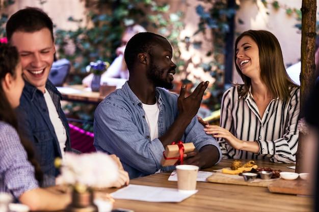 Charla informal con los mejores amigos en el restaurante en un cálido día de verano.