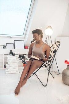 Charla telefónica. elegante mujer de piel oscura guapa sentada y hablando por teléfono
