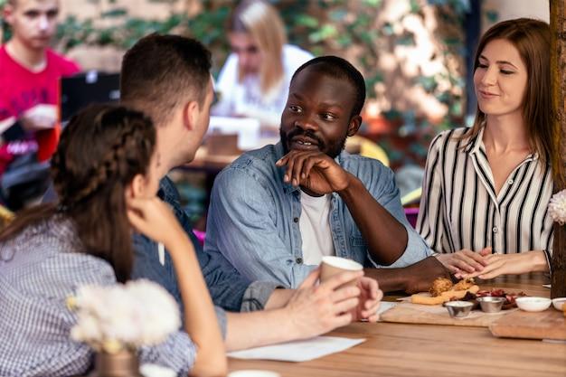 Charlando con los mejores amigos en el acogedor restaurante al aire libre en el cálido día de verano
