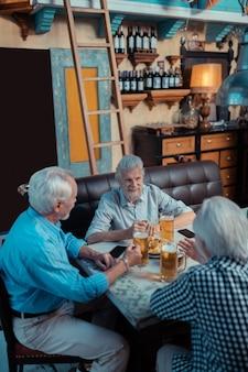 Charlas y copas. vista superior de tres hombres alegres canosos hablando y bebiendo cerveza