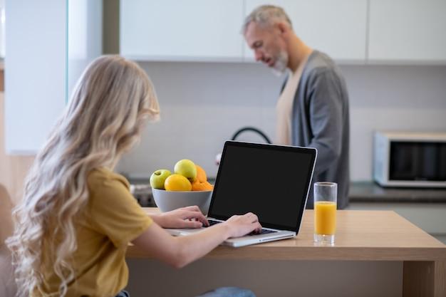 Charlas matutinas. una chica rubia sentada en la cocina y hablando con su papá.