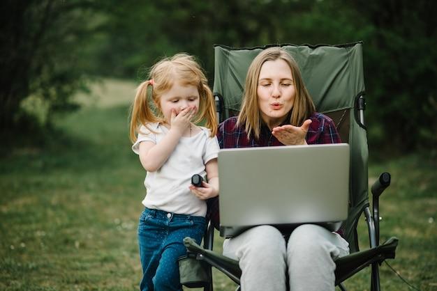 Chatear en línea con la familia en la computadora portátil en un picnic en la naturaleza