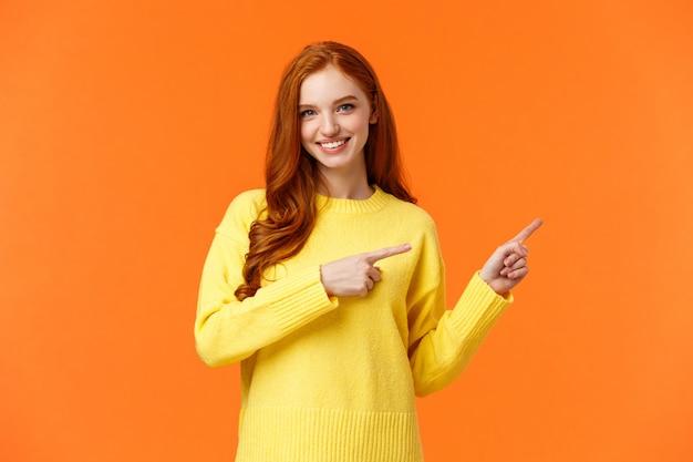 Cheeky hermosa niña sonriente con el pelo rizado rojo, apuntando hacia la derecha, aconseja qué visita de la tienda, recomienda una tienda en línea para artículos de invierno