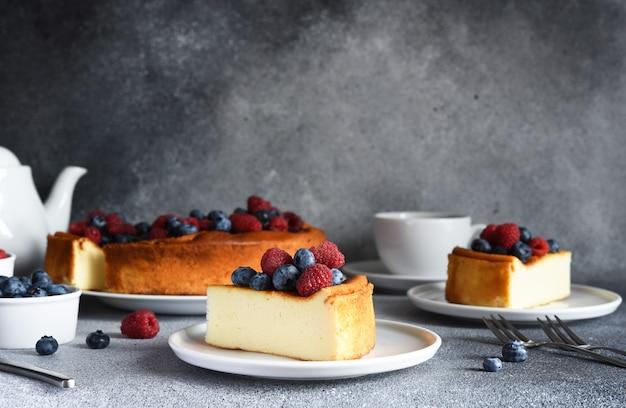 Cheesecake new york rebanada de tarta de queso con frutos rojos y una taza de té