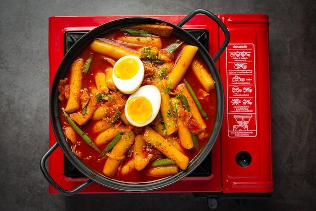 Cheesy tokbokki comida tradicional coreana sobre fondo de tablero negro. plato de almuerzo.