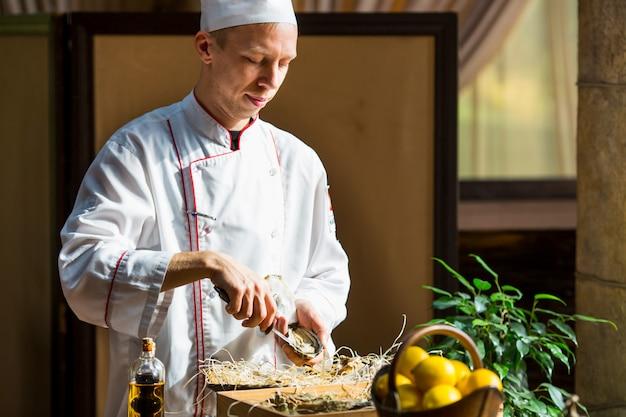 Chef abre ostras frescas en un restaurante