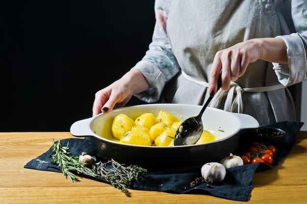 El chef adoba las papas con especias, aceite de oliva y mantequilla.