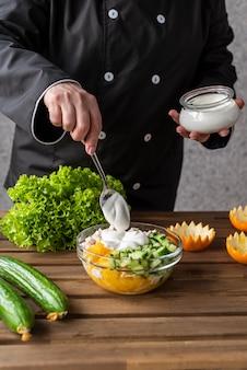 Chef agregando aderezo a la ensalada