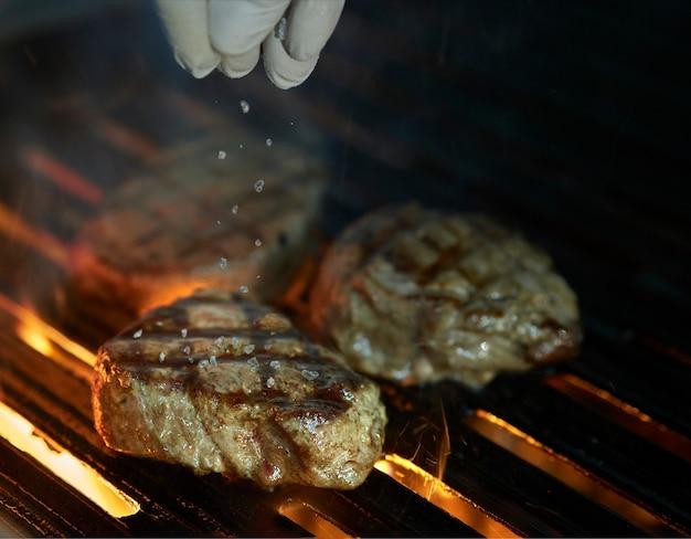 Chef agregando sal al centro del bistec a la parrilla con llamas y humo