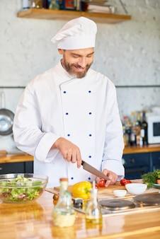 Chef alegre trabajando en la cocina del restaurante