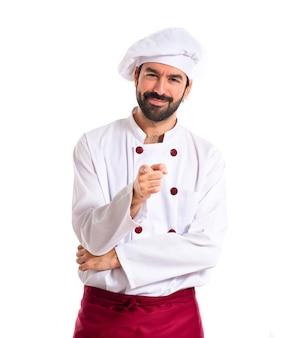Chef apuntando a la parte delantera sobre fondo blanco
