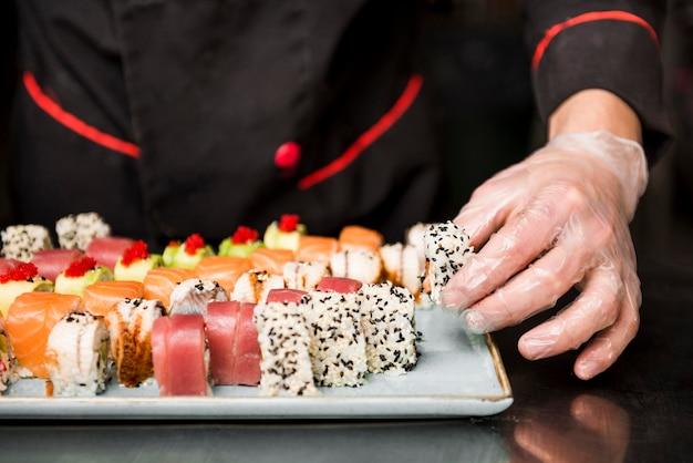 Chef arreglando sushi fresco de cerca
