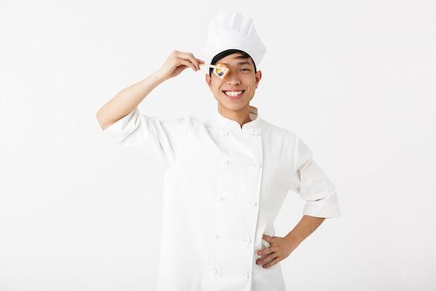 Chef asiático emocionado vistiendo uniforme que se encuentran aisladas sobre la pared blanca, preparando sushi