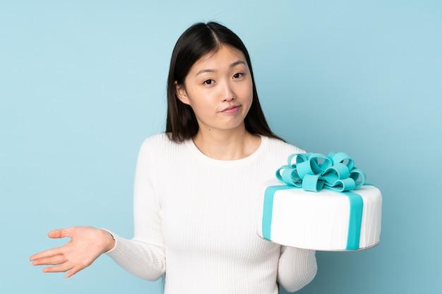 Chef asiático pastelero sosteniendo un gran pastel en la pared azul haciendo dudas gesto mientras levanta los hombros