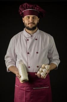 Chef barbudo alegre en uniforme con delantal violeta y gorra sosteniendo una botella de leche y media docena de huevos