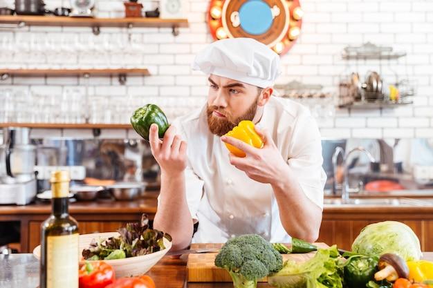 Chef barbudo pensativo eligiendo verduras frescas para ensalada en la cocina
