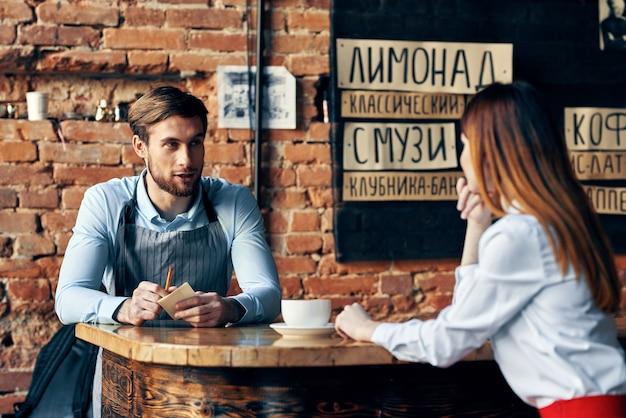 Chef camarero toma un pedido de una mujer joven en una camisa una taza de café restaurante cafetería