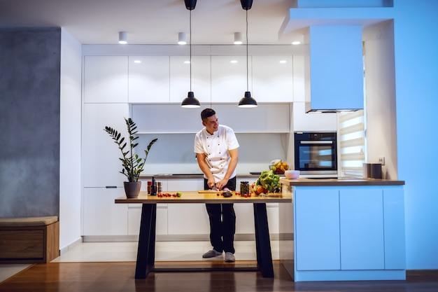 Chef caucásico en uniforme blanco para picar cebolla y preparar comida