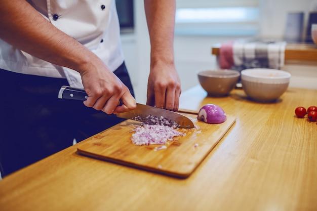 Chef caucásico en uniforme de pie en la cocina doméstica y cortar la cebolla