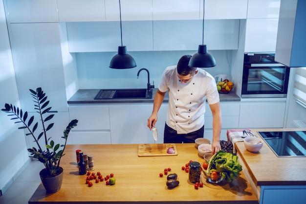 Chef caucásico en uniforme de pie en la cocina, sosteniendo un cuchillo y preparando la cena