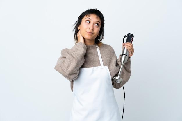 Chef chica uruguaya con batidora de mano sobre pared blanca pensando una idea
