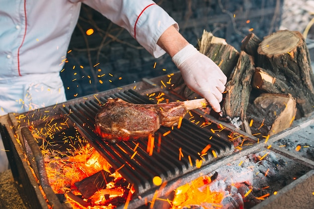 Chef cocina bistec. cook enciende la carne al fuego.