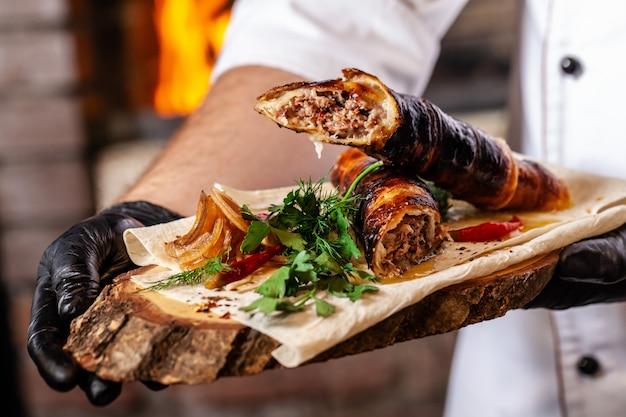 Chef cocina carne kebab lyulya en la masa a la parrilla.