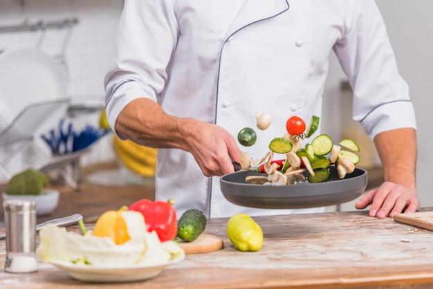 Chef en cocina cocinando con verduras