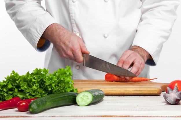 Chef cocina ensalada de vegetales frescos en su cocina