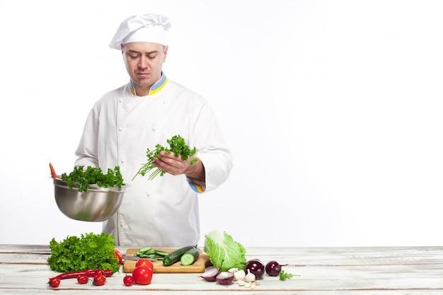 Chef cocina ensalada de verduras frescas en su cocina