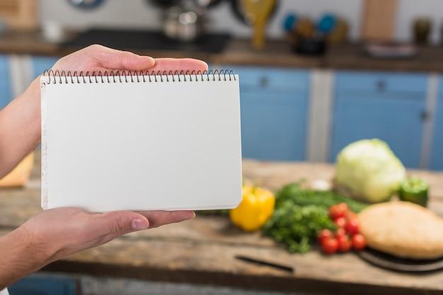 Chef en cocina enseñando libreta